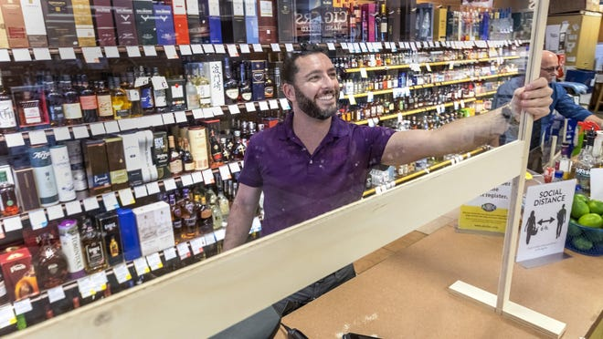 Nathan Dale, area sales manager, installs plexiglass partitions for the protection of their employees at the ABC Fine Wine & Spirits location on South Dixie Highway in West Palm Beach Friday afternoon, March 27, 2020.