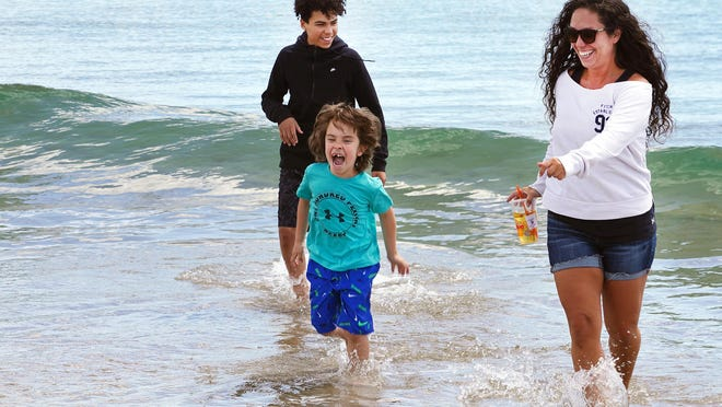 Falicia Escobar and her sons Christian, 12, left, and Jaxson 5, react to the cold ocean water Monday morning at Hampton Beach. The sand opened to beachgoers for the first time since March, but only for transitory activities like walking and swimming.