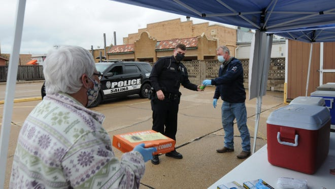 Karen Olson, left, brings Salina police officer Jacob Hansel a Little Caesars pizza as Terry Oehmke hands Hansel a cold soda during the grab-and-go pizza and pop event to support local first responders Friday in the Immanuel Lutheran Church parking lot.