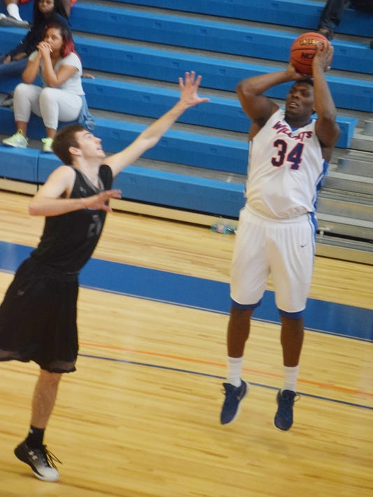 Louisiana College's Brandon Watkins (34, right) shoots a three-pointer over the University of the Ozarks Dillon Gash (21, left).