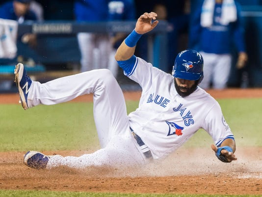 Toronto Blue Jays' Jose Bautista comes into score against the New York Yankees during the seventh inning of a baseball game in Toronto, Friday, Sept. 23, 2016. (Mark Blinch/The Canadian Press via AP)