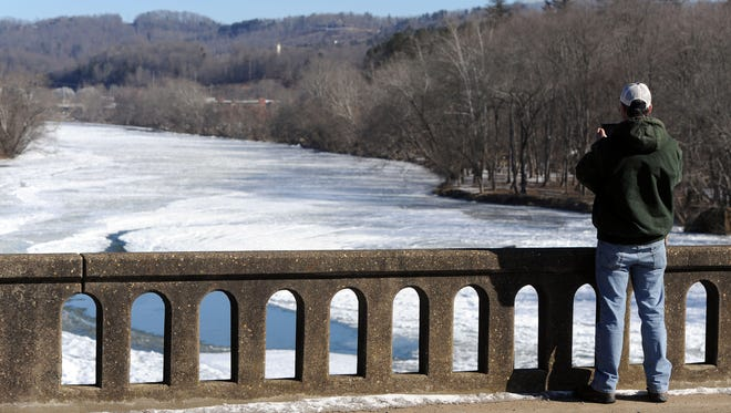A man takes a picture of the frozen French Broad River from the Old Leicester Highway over the river Friday morning.