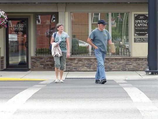 Terri and Jim Ahlefeld of Crestline safely cross Sandusky