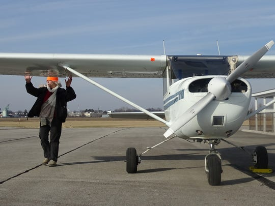 Peg Ballou does a pre-flight inspection of the wing of her Cessna 150 Monday at Bucyrus Municipal Airport.