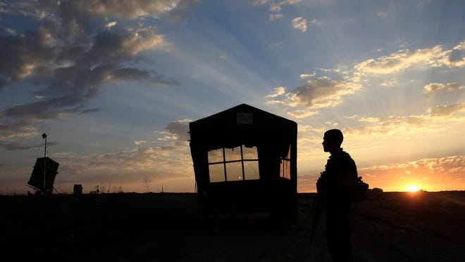An Israeli soldier stands near an Iron Dome anti-missile battery system, on the far left, near the southern city of Sderot, Israel, on Wednesday.