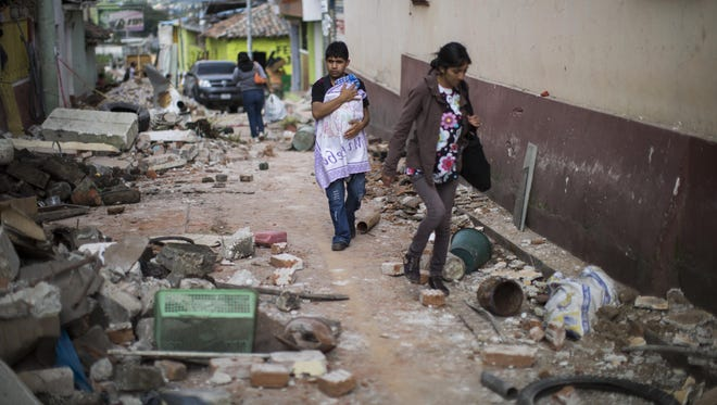 A Family walks trough a street littered with the rubble from buildings that fell during an earthquake in San Pedro, Guatemala, Monday, July 7, 2014. An earthquake measuring 6.9 on the Pacific Coast shook a wide area of jQuery17205575694739818573_1404818912090southern Mexico and Central America Monday. (AP Photo/Luis Soto)