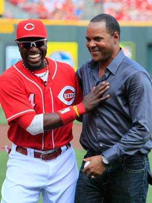 Cincinnati Reds second baseman Brandon Phillips (4) talks with former Reds shortstop Barry Larkin during ceremonies retiring Larkin's number prior to a baseball game against the St. Louis Cardinals, Saturday, Aug. 25, 2012, in Cincinnati. (AP Photo/Al Behrman)