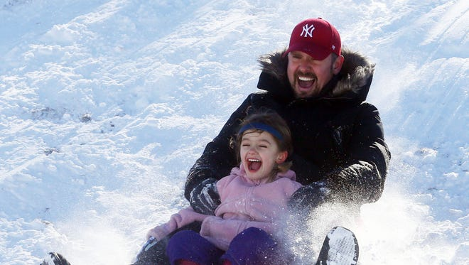 Nathaniel Johnston of Dobbs Ferry and his daughter Anika, 6, speed down a hill at Gould Park in Dobbs Ferry Jan. 24, 2016. Saturday's snow storm gave parents the opportunity to spend Sunday out enjoying the sunny winter day with their kids.