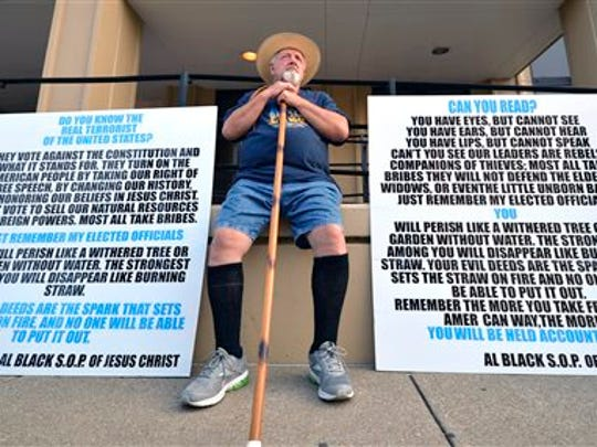 Al Black of Proctorville, Ohio,  sits in protest in front of the Carl D. Perkins Federal Building in Ashland, Ky., Thursday, Sept. 3, 2015. Black, a supporter of Rowan County Clerk Kim Davis, was waiting for her arrival as she was ordered to appear in Federal Court to explain why she is refusing to issue marriage licenses despite a federal order to do so.