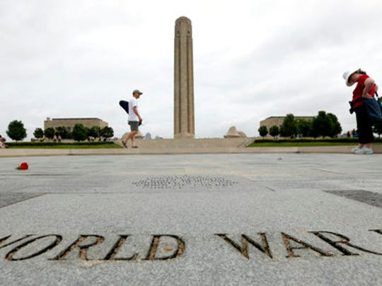 """FILE - In this May 26, 2014 file photo, visitors look at memorial bricks after a Memorial Day observance at the National World War Museum at Liberty Memorial in Kansas City, Mo. Foreign dignitaries from around the globe are converging on Kansas City, Missouri, and its towering World War I monument to observe the centennial of the day the U.S. entered """"The Great War."""" A sellout gathering of 3,000 onlookers also have snapped up tickets for the daylong observance Thursday, April 6, 2017,  titled """"In Sacrifice for Liberty and Peace."""""""