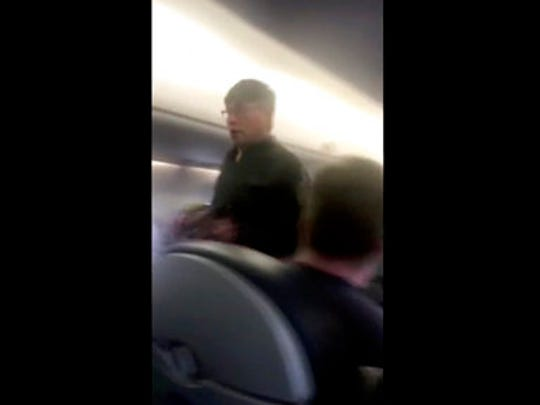 This Sunday, April 9, 2017, image made from a video provided by Audra D. Bridges shows a passenger who was removed from a United Airlines flight in Chicago. Video of police officers dragging the passenger from an overbooked United Airlines flight sparked an uproar Monday on social media, and a spokesman for the airline insisted that employees had no choice but to contact authorities to remove the man.