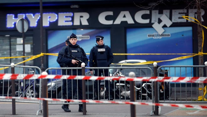 Police officers stand in front of HyperCasher supermarket at Porte de Vincennes in eastern Paris on Jan. 10, 2015, a day after a gunman took hostages there.