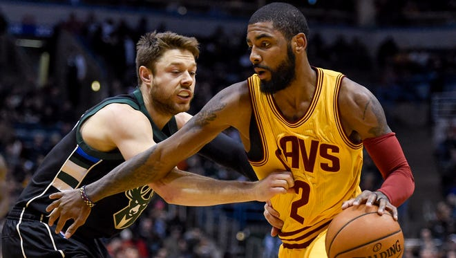 Cavaliers guard Kyrie Irving drives for the basket against Bucks guard Matthew Dellavedova.