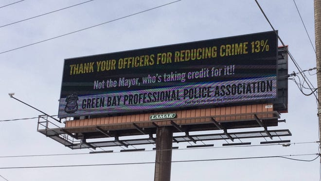 The Green Bay Professional Police Association billboard accuses Green Bay Mayor Jim Schmitt for taking for a reduction in crime. The billboard is along the Don A. Tilleman Bridge, which carries Mason Street traffic over the Fox River.