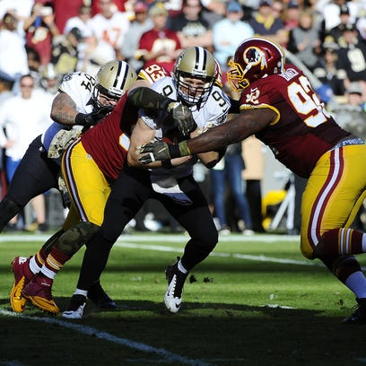 Saints quarterback Drew Brees (9) is sacked by Redskins defensive end Chris Baker (92) and outside linebacker Trent Murphy (93) during the Nov. 15 game.