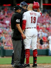 Cincinnati Reds first baseman Joey Votto (19), right, and Milwaukee Brewers catcher Erik Kratz (15), left, exchange words at home plate in the third inning during a National League baseball between the Milwaukee Brewers and the Cincinnati Reds, Thursday, June 28, 2018, at Great American Ball Park in Cincinnati.