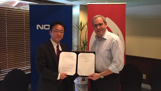 DOCOMO PACIFIC president and CEO Jonathan Kriegel and Jae Won, head of Nokia Japan, announce their memorandum of understanding on Wednesday.