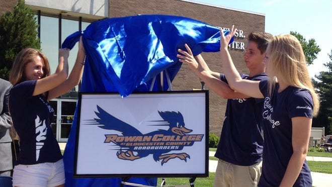 Students unveil the new athletic logo for Rowan College of Gloucester County during a ceremony July 1.