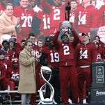 Head Coach Nick Saban applauds as running back and Heisman trophy winner Derrick Henry, (2), hoists the coach's trophy, Saturday, Jan. 23, 2016, in Tuscaloosa, Ala. Alabama football fans turned out by the thousands to celebrate the Crimson Tide's fourth national championship in seven years. (AP Photo/Hal Yeager)