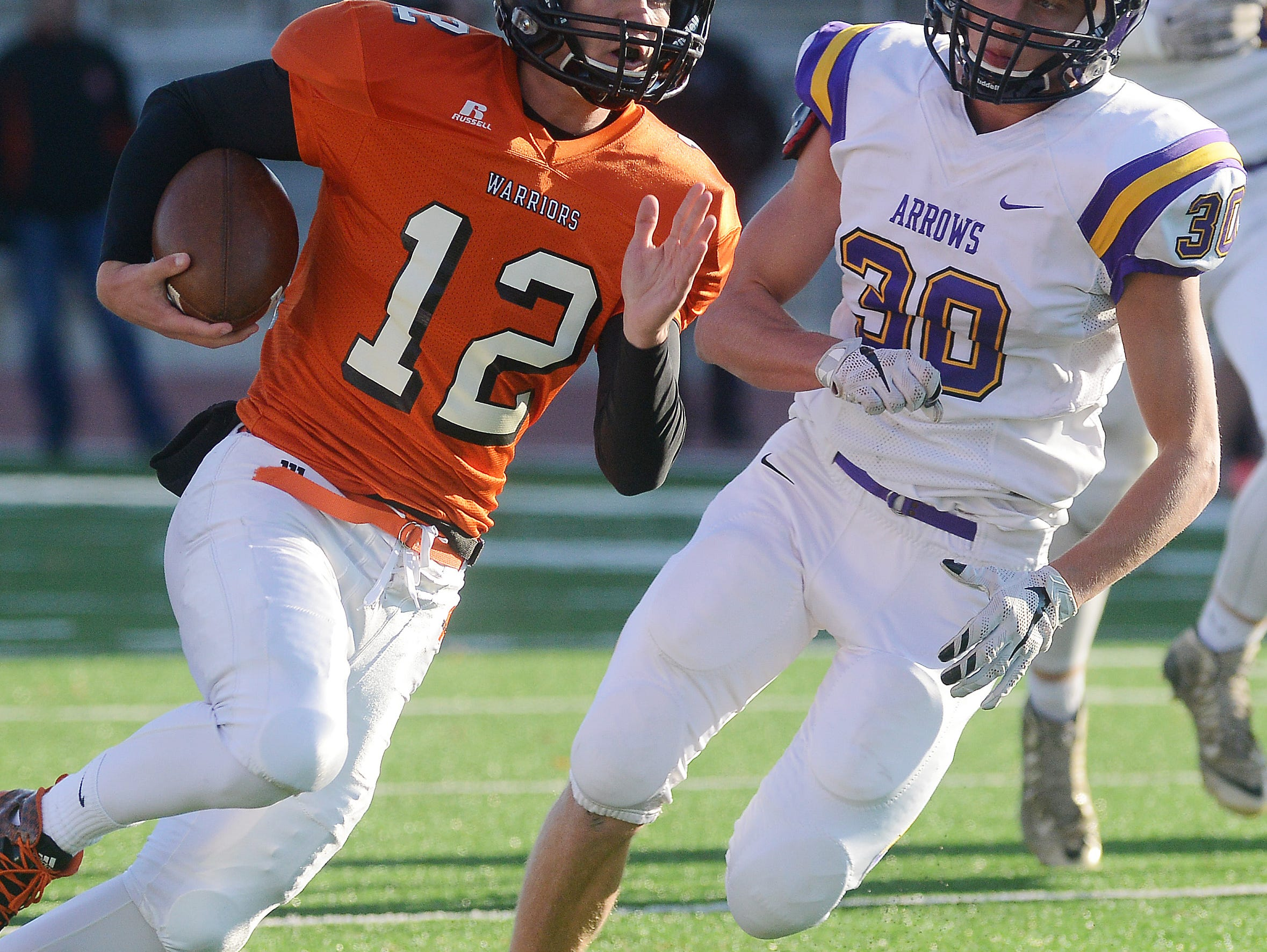 Washington quarterback, Jack Schelhaas carries the ball with Watertown's Parker Schulz on his heels in a class 11AAA football quarterfinal Thursday night at Howard Wood Field, Oct 29, 2015.