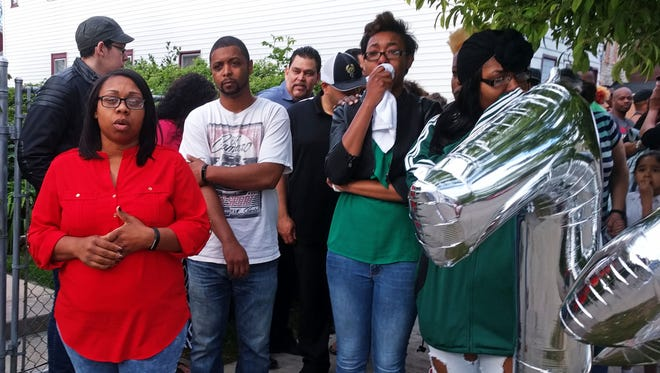 Ald. Chantia Lewis (left) speaks at a vigil for Phillip Franklin, who died last week in a hit-and-run accident at S. 13th St. and W. Greenfield Ave. Second from right  is one of Franklin's daughters, Azariah Franklin, 18.