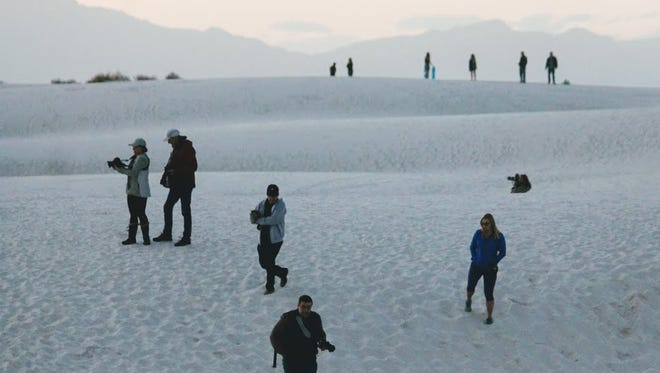 Hundreds of people climbed the fence along U.S. Highway 70 West to gain access to White Sands National Monument during the federal government shutdown Saturday.