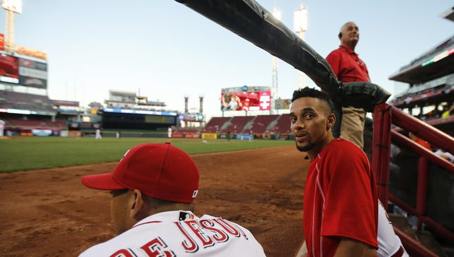 Reds center fielder Billy Hamilton turns back to the fans as shortstop Ivan De Jesus and catcher Ramon Cabrera watch the Sept. 12 game with him in the second inning.
