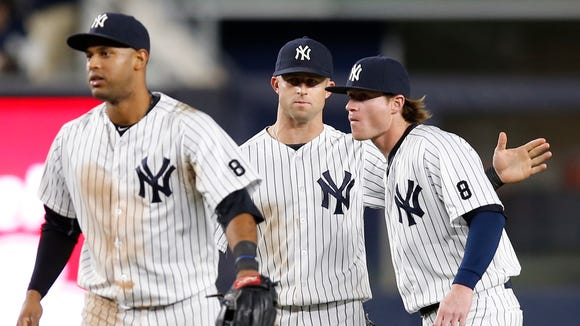 New York Yankees center fielder Aaron Hicks, left, left fielder Brett Gardner, center,  and right fielder Ben Gamel (38) celebrate after the Yankees defeated the Kansas City Royals 10-7 in a baseball game at Yankee Stadium in New York, Tuesday, May 10, 2016.
