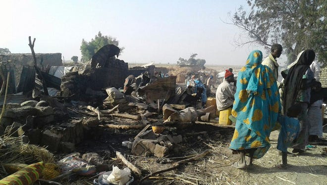 People standing next to the destruction after an air force jet accidentally bombarded a camp for those displaced by Boko Haram Islamists, in Rann, northeast Nigeria, on Jan. 17. 2017.