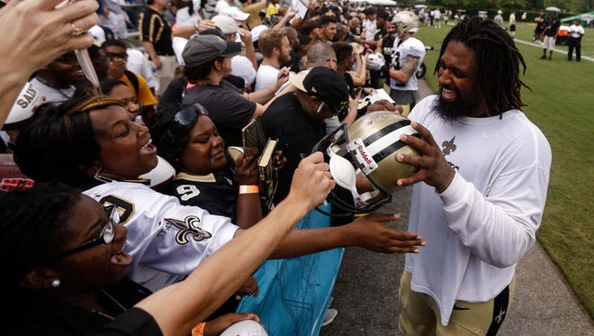 New Orleans Saints defensive end Cameron Jordan (94) signs autographs for fans following a practice training camp practice at the Metairie Training Facility.