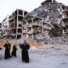 Palestinian women look at the shattered remains of a building complex that was destroyed by fighting between Hamas Militants and Israel on August 29 in the northern Gaza Strip city of Beit Hanun.