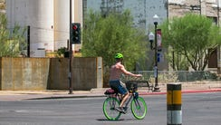 A bicyclist bikes down Mill Avenue past the Hayden