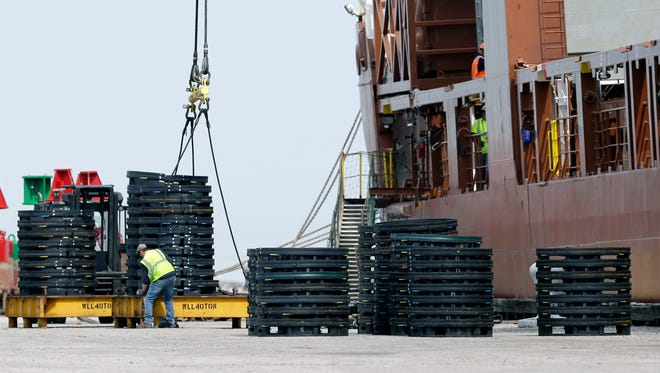 A worker fastens chains to load materials on the Amsterdam-bound Fortunagracht at the Port of Cleveland in Cleveland.