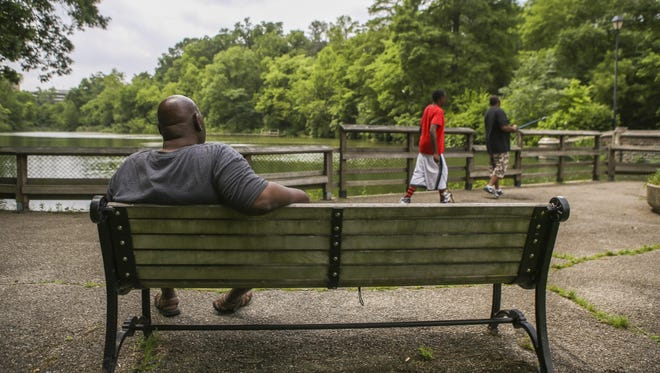 People enjoy the view of the lake at Burnet Woods on a summer afternoon. A letter writer asks others to support the parks levy to help clean up the park and make it safer.