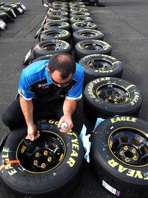 A crew member glues lug nuts onto a tire.