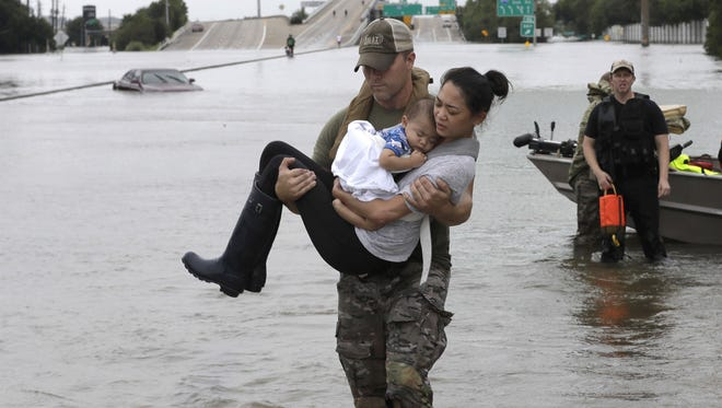 CORRECTS FROM CONNIE TO CATHERINE - Houston Police SWAT officer Daryl Hudeck carries Catherine Pham and her 13-month-old son Aiden after rescuing them from their home surrounded by floodwaters from Tropical Storm Harvey Sunday, Aug. 27, 2017, in Houston. The remnants of Hurricane Harvey sent devastating floods pouring into Houston Sunday as rising water chased thousands of people to rooftops or higher ground. (AP Photo/David J. Phillip) ORG XMIT: TXDP128