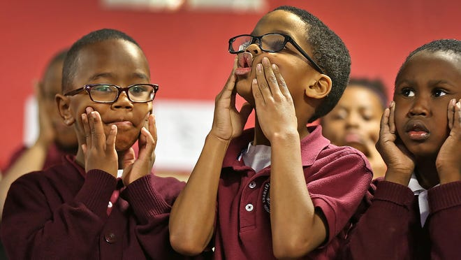 Javarius Strayhorn, from left, King Stokes, and Alex Cooper warm up their faces as they join other students going through rhythmic exercises in music class at Tindley Genesis Academy, Thursday, October 29, 2015. The K-3 charter school infuses music into the daily curriculum.