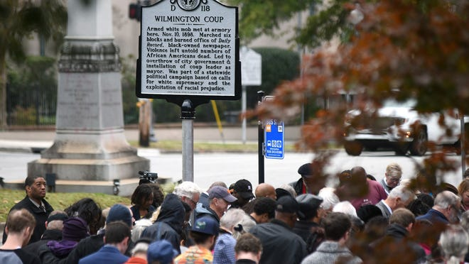 People stand under a North Carolina highway historical marker to the 1898 Wilmington Coup shortly after it was unveiled during a dedication ceremony in downtown Wilmington in 2019. The marker stands outside the Wilmington Light Infantry building, the location where a mob of white supremacists originally gathered.