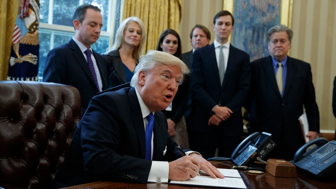 President Donald Trump signs an executive order on the Keystone XL pipeline, Tuesday, Jan. 24, 2017.