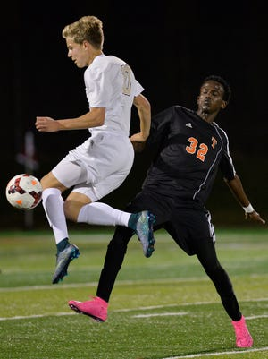 East Ridge's Grant Tostenrud (10) beats St. Cloud Tech's Abdiqudar Farah (32) to the ball during the first half of their State Class 2A semifinal game Monday at Husky stadium. East Ridge won 2-0.