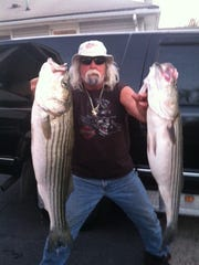 Mike Yaros, Perth Amboy, with two striped bass he caught