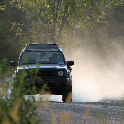 A car kicks up a trail of dust as it travels along