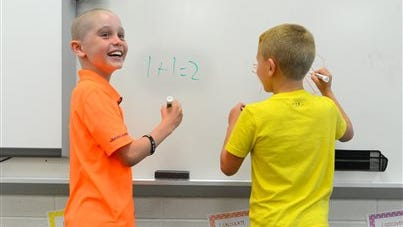 Braxton Voss, left, and his twin brother Bentlee work at the white board on Monday in Priceville, Ala.  Braxton, who was diagnosed with leukemia just hours after finishing his first day of school last year, has been cleared to rejoin his classmates. He will be among the more than 8,000 Morgan County students to return when classes resume today.