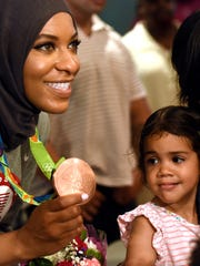 "The New Jersey chapter of the Council on American-Islamic Relations presented Olympic bronze medalist Ibtihaj Muhammad with the ""Breaking Barriers Award"" at a parade held in her honor last year in Maplewood. Here she displays her bronze medal in front of Isabel Valadez, 3, and her mother, Nora Rodriguez of Maplewood, at the Burgdorff Performing Arts Center, where Ibithaj signed autographs."