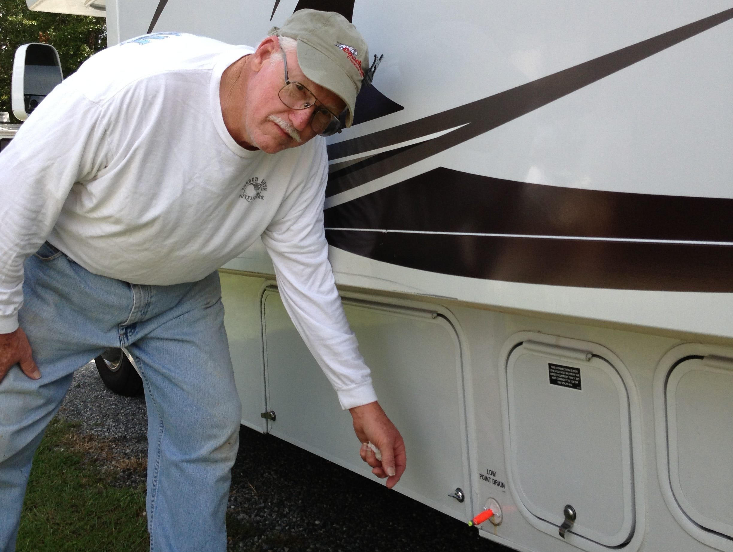 John Newham inserts a fishing lure as a makeshift plug for the leaking low-point drain.
