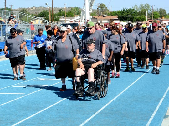 Team Artesia walks down the track during the opening