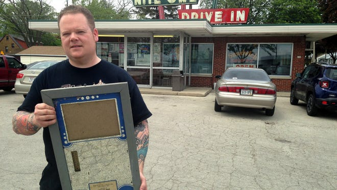 Chris Roepke, owner of the Nite Owl Drive In, 830 E. Layton Ave., holds the frame that used to display a photo of a record-setting musky. This week, someone stole the photo from the mirrored frame, which was hanging in the restaurant's men's restroom.