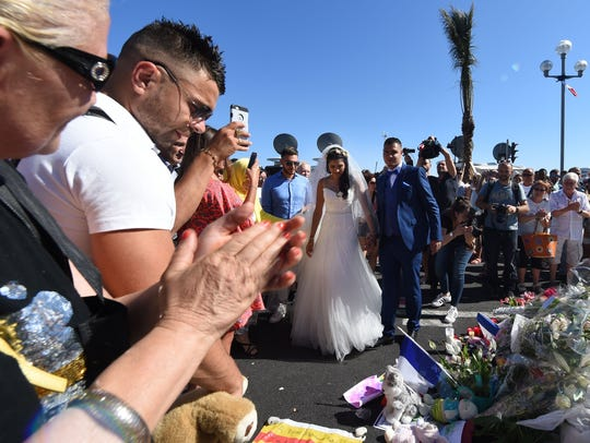 People applaud after newlyweds laid flowers on the