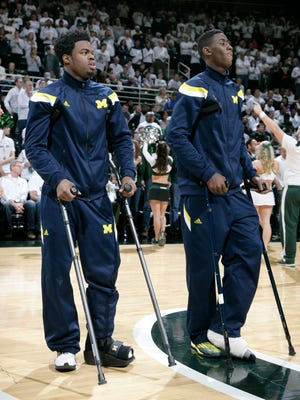 Injured Michigan players Derrick Walton Jr., left, and Caris LeVert watch warmups while standing on crutches before an NCAA college basketball game against Michigan State, Sunday, Feb. 1, 2015, in East Lansing, Mich. Michigan State won 76-66 in overtime.