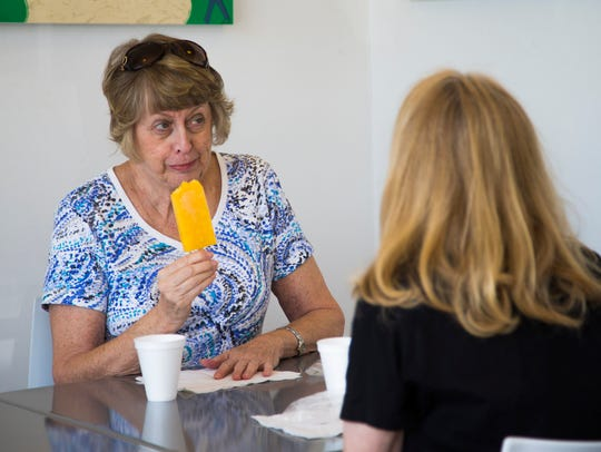 Cheryl Stillman (left) and Kim Rexing enjoy their popsicles